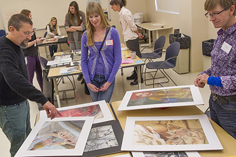 Student shows presents her portfolio to two observing professors
