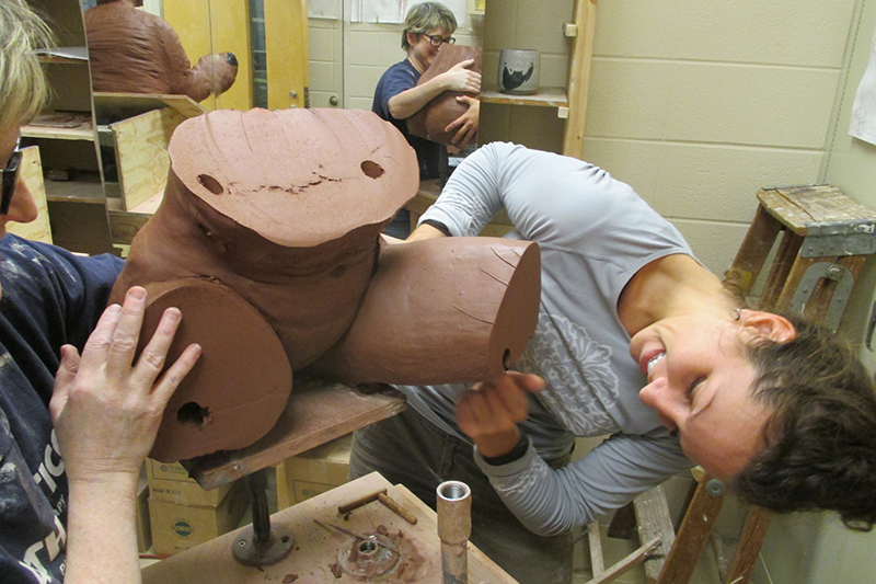 student works on a ceramics sculpture of a human torso