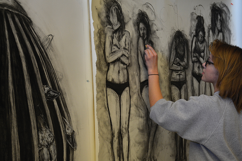 student works on a drawing