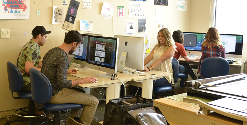 students work at computers on visual communication projects