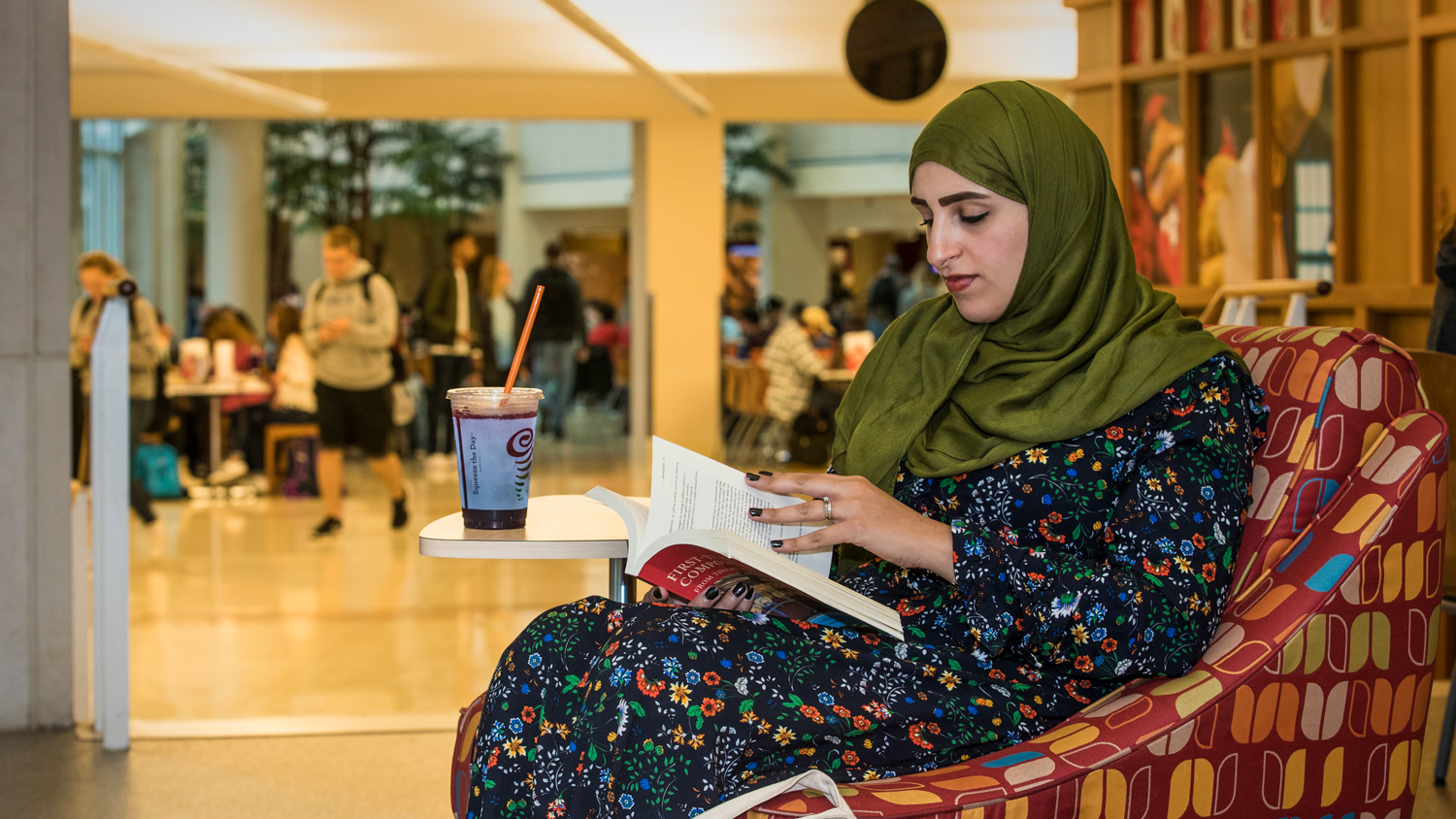 international student reading in the Atrium
