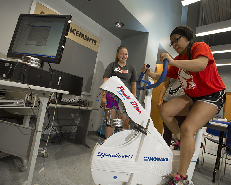 students working with a stationary bike in the Human Performance Laboratory