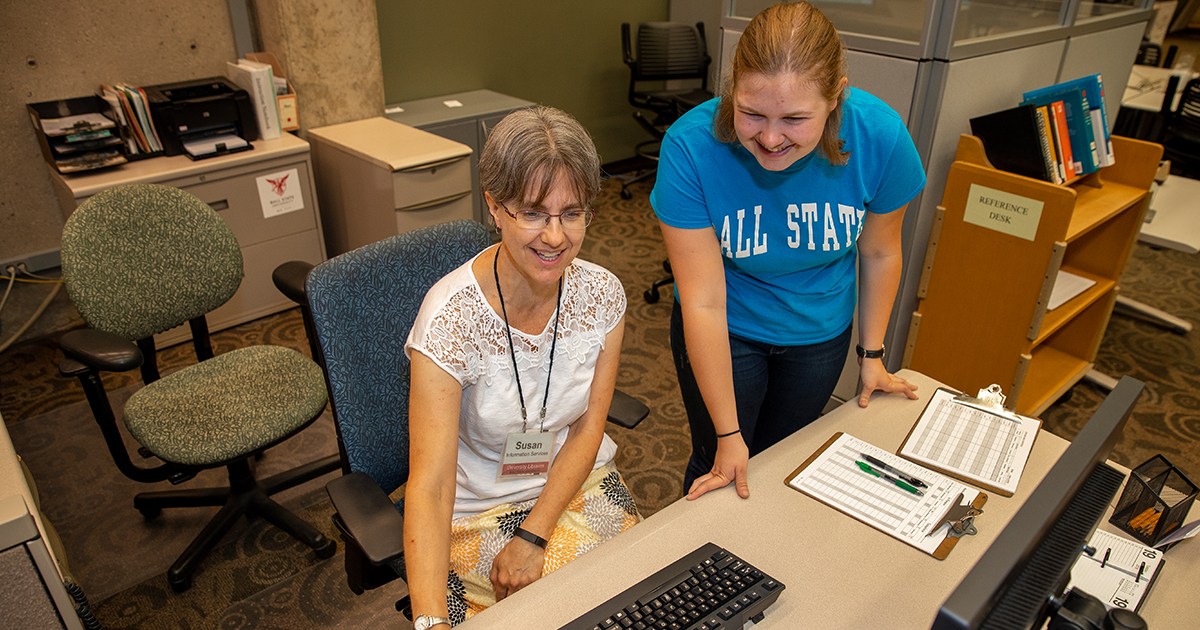 A Ball State student gets help from an employee of the Library