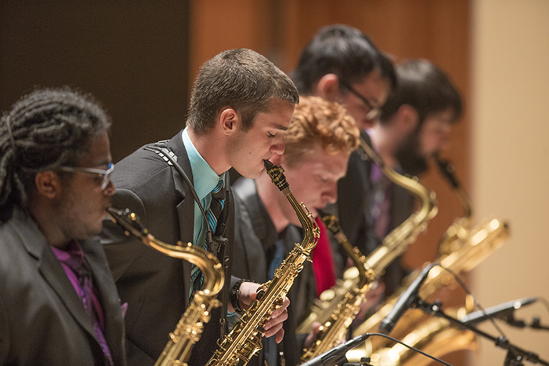 male students performing with saxophones on stage