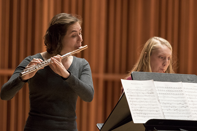 female students play flutes on stage