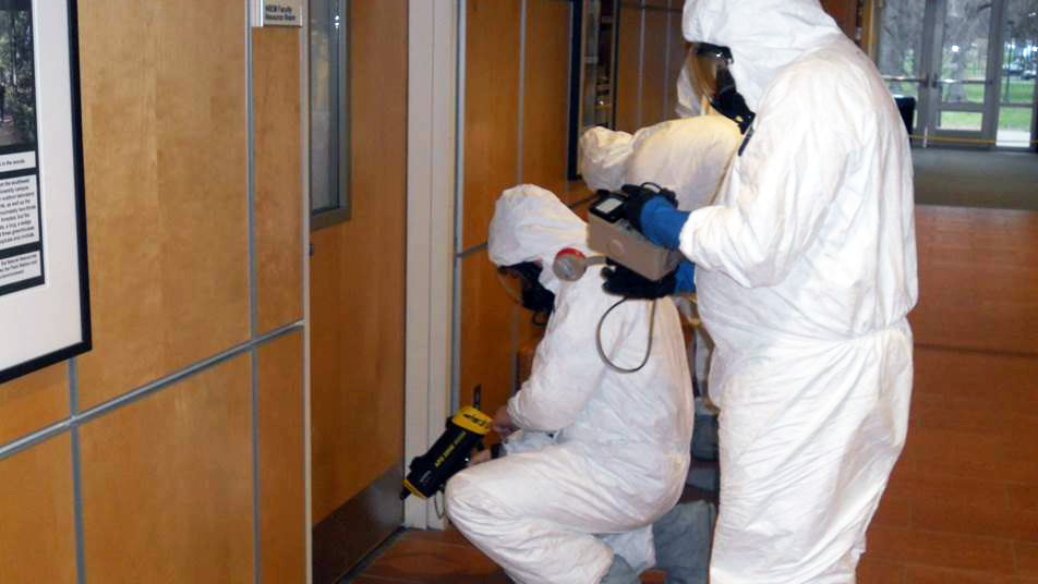 people wearing hazmat suits conduct an inspection