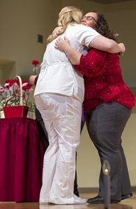 student and instructor hugging during pinning ceremony