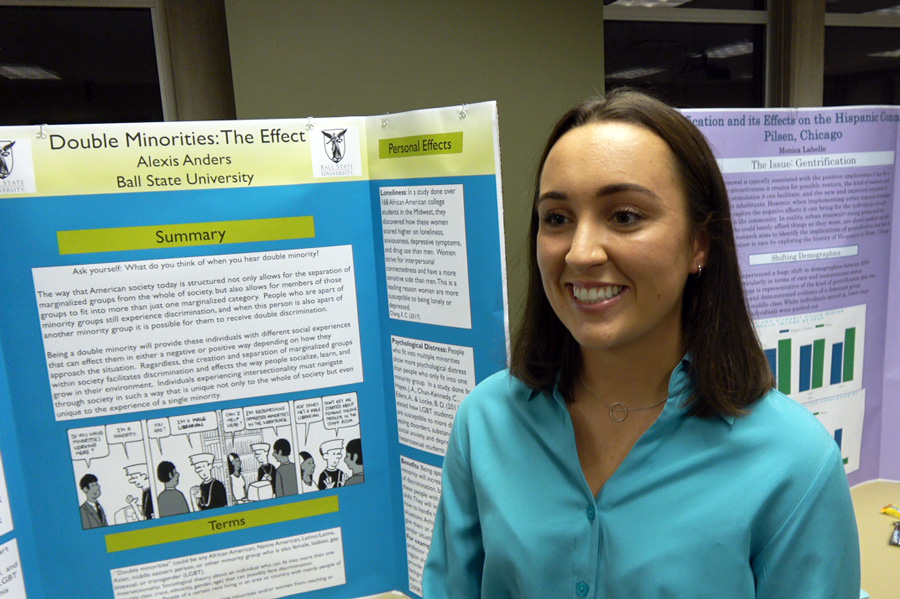 woman standing with research poster
