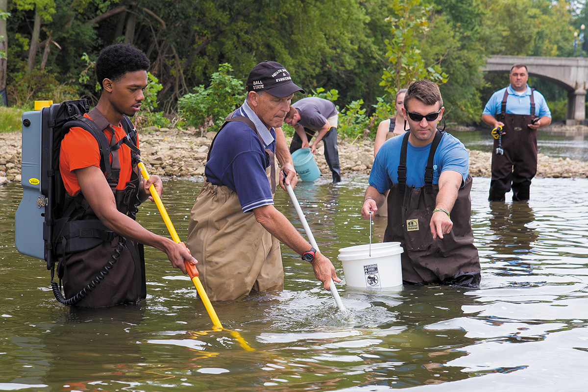 students and faculty working in river